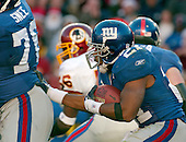 Landover, MD - December 24, 2005 -- New York Giant running back Tiki Barber (21) follows his blocker, Chris Snee (76) after taking a hand-off from Eli Manning (10) in first half action against the Washington Redskins at FedEx Field in Landover, MD on December 24, 2005.  The Redskins won the game 35 - 20..Credit: Ron Sachs / CNP.(RESTRICTION: NO New York or New Jersey Newspapers or newspapers within a 75 mile radius of New York City)