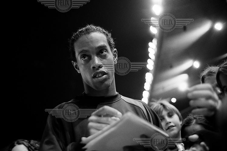 FC Barcelona football player Ronaldinho signs autographs for children during a teaching session conducted by the team.