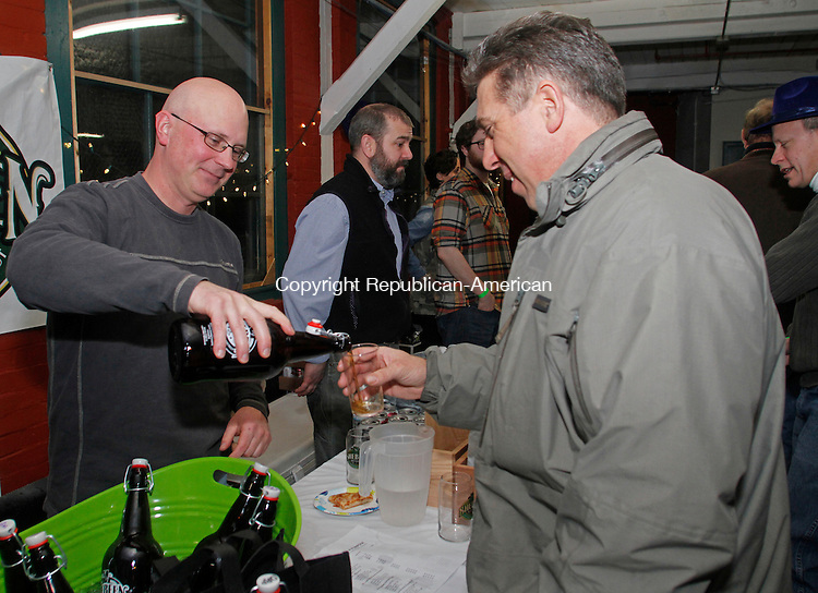 Winsted, CT-011814MK11 Jeff Roberts from Shebeen Brewery pours a sample to Mark Bigos, from Torrington, during the first annual Pints for a Purpose beer tasting and a concert to benefit the Northwest YMCA's Strong Kids campaign at Whiting Mills Saturday night in Winsted. Winsted YMCA branch director Jay Cohen said over a hundred beer enthusiasts came to enjoy seventeen local breweries and the proceeds will benefit the local community and families in need. Michael Kabelka / Republican-American