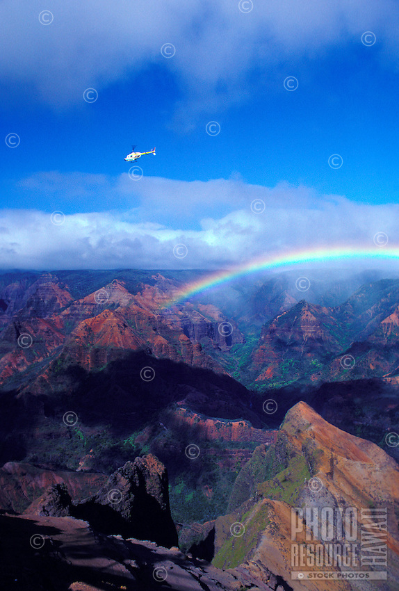 A helicopter flies above a rainbow spanning the incredible rock formations at Waimea Canyon on Kauai.