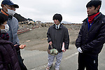 Masaya Ito (C) shows a bank book he has found to Seiko Tsuda (L), her husband Hiroshi (2L) and their son Naoki (R) while searching for his younger brother in Rikuzentakata, Iwate Prefecture, Japan on  22 March 20011.  .Photographer: Robert Gilhooly