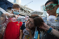 A pro-democracy protester has pepper spray washed from her eyes by sympathetic supporters as they block the the main highway through Admiralty, next to the Hong Kong government headquarters in Hong Kong's downtown district, on the first day of the mass civil disobedience campaign Occupy Central, Hong Kong, China, 28 September 2014.