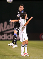 Ryan Cochrane (5) heads the ball over Jovan Kirovski (right). San Jose Earthquakes tied Los Angeles Galaxy 1-1 at the McAfee Colisum in Oakland, California on April 18, 2009.