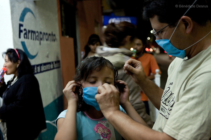 April 24, 2009 - Mexico City, Mexico - A father fits his daughter with a newly purchased surgical mask that the governement of Mexico is recomending all residents of the city wear. Photo credit: Benedicte Desrus / Sipa Press