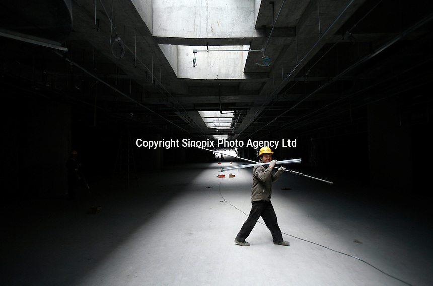 A worker carries construction materials at the nearly-completed new terminal of the Pudong Airport expansion project in Shanghai, China..12 Mar 2007
