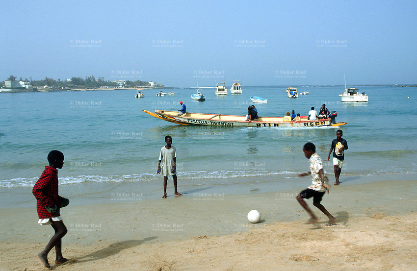 Senegal. Dakar. Ngor beach. Young boys play football on the beach while a motor boat takes tourists on a boatride in the sea. © 2000 Didier Ruef