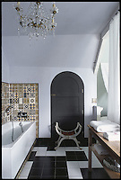 This suite bathroom at La Seigneurie is decorated with a surprising combination of antique tiles and a 1950s black and white tiled floor and is furnished with a Napoléon III stool and side table