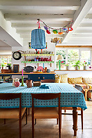 In the spacious kitchen the floor has been dug out to provide extra height and the beams are painted white to create a sense of space. The tablecloth, lampshade and curtains are  in Molly Mahon fabrics.