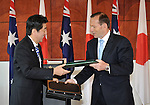 AUSTRALIA, Canberra : Japanese Prime Minister Shinzo Abe (L) and Australian Prime Minister Tony Abbott (R) exchange documents after signing the Japan - Australia Economic Agreement and the Agreement on the Transfer of Defence Equipment and Technology, at Parliament House in Canberra on July 8, 2014. Defence ties are set to take centre stage when Australia plays host to Japanese Prime Minister Shinzo Abe this week, as the two countries look set to strengthen their relationship through annual leaders' meetings. AFP PHOTO / Mark GRAHAM
