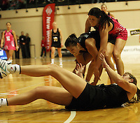 Irene Van Dyk falls over as Liana Barrett-Chase retrieves the ball under pressure from Peta Scholz during the International  Netball Series match between the NZ Silver Ferns and World 7 at TSB Bank Arena, Wellington, New Zealand on Monday, 24 August 2009. Photo: Dave Lintott / lintottphoto.co.nz