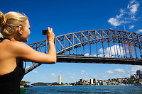A woman photographs the Sydney Harbour Bridge.  Sydney, New South Wales, AUSTRALIA