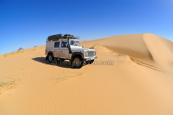 Africa, Mauritania, Sahara Desert. Land Rover Defender TD5 Station Wagon crossing sand dunes between Choum and Atar. --- RELEASES AVAILABLE! Automotive trademarks are the property of the trademark holder, authorization may be needed for some uses.