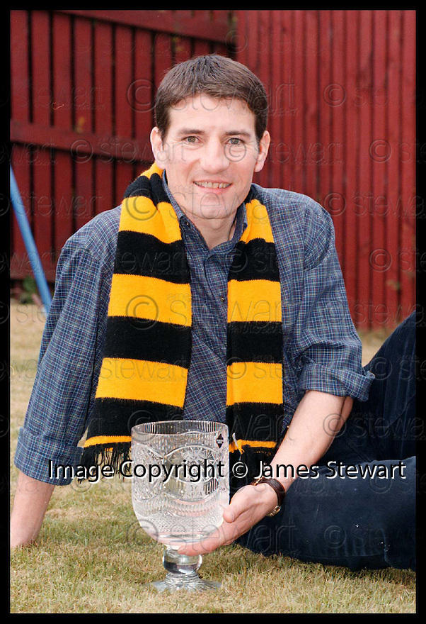 27th April 98  Ref : 980211 Copyright Pic : James Stewart   .ALLOA'S WILLIE IRVINE RELAXES AT HIS FALKIRK HOME WITH HIS THIRD DIVISION PLAYER OF THE YEAR TROPHY.......Payments to :-.James Stewart Photo Agency, Stewart House, Stewart Road, Falkirk. FK2 7AS      Vat Reg No. 607 6932 25.Office : 01324 630007        Mobile : 0421 416997.If you require further information then contact Jim Stewart on any of the numbers above.........