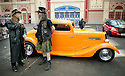 LONDON INTERNATIONAL CLASSIC AND CUSTOM SHOW  - Alexandra Palace  - 26.2.12.Musician Peter Sayers  a customised  fan in front of a bright orange Ford 3 window coupe...Picture by Gavin Rodgers/ Pixel8000. 07917221968