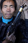 A man with his shot gun posing for camera. Villagers in Bai Sha are the only Miao people still allowed to keep their firearm by government. Congjiang County. Guizhou Province. China