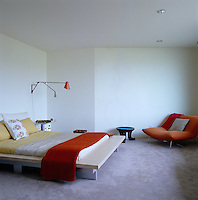 The carpeted bedroom is simply furnished with a large comfortable chair and a platform bed