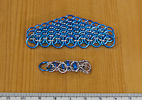 "Mick and my first chain mail (chainmail, maille, etc.) projects.  The upper one is a dragonscale weave using blue anodized aluminum and bright aluminum rings.  The lower project is captive inverted round weave with 20ga 5/32"" ID turquoise anodized aluminum rings and 20ga 3/16"" ID bright aluminum rings.  The large blue ring on the lower project is a placeholder."