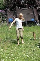 Rehkitz, Reh-Kitz, verwaistes, pflegebedürftiges Jungtier wird in menschlicher Obhut großgezogen, Kind, Mädchen spielt und tobt mit zahmen Kitz im Garten, Tierkind, Tierbaby, Tierbabies, Europäisches Reh, Ricke, Weibchen, Capreolus capreolus, Roe Deer, Chevreuil