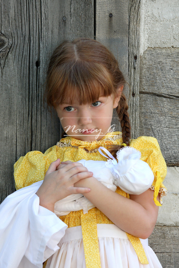 A young girl dressed in a prairie with a doll dress historical reenactment