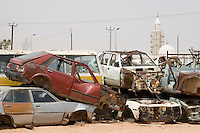 Bir al-Ghanam, south of Tripoli, Libya - Wrecked Cars Attest to Libya's High Traffic Accident Rate.  Mosque in Background.