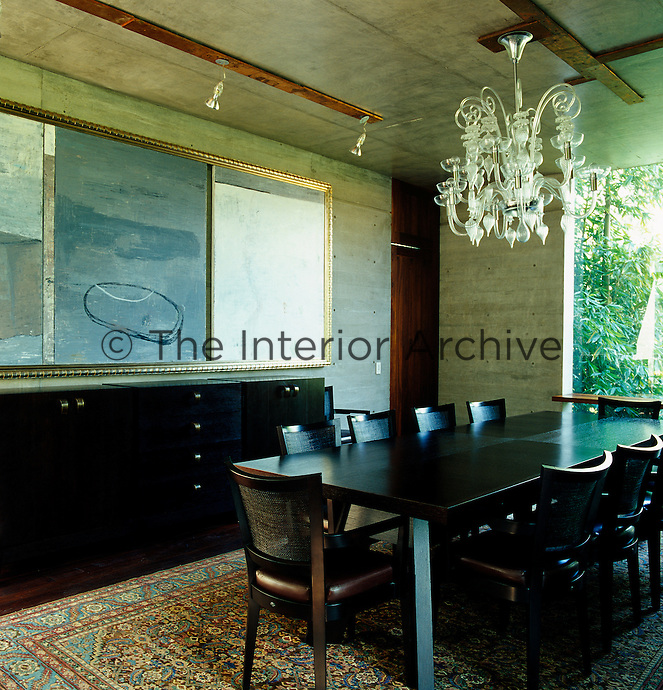 The heavy masculine dining room has a crystal chandelier hanging from a concrete ceiling above the table