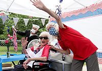 Rita Miller, 100, waves with her daughter Carolyn Miller (right) and friend Russ Richman Tuesday, June 23, 2020, as they watch a surprise birthday parade in her honor. Miller is a World War II veteran that served in the Army Nurse Corp. The surprise parade included friends, family and the city of Fayetteville Fire and Police Departments. Miller also received recognition from local, state and national officials. Check out nwaonline.com/200624Daily/ and nwadg.com/photos for a photo gallery.<br /> (NWA Democrat-Gazette/David Gottschalk)