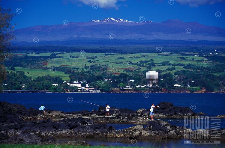 Men fishing in Hilo bay with town in rear and Mauna Kea,  Big Island of Hawaii