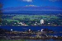 Men fishing in Hilo bay with town in rear and Mauna Kea,  Big Island of Hawaii