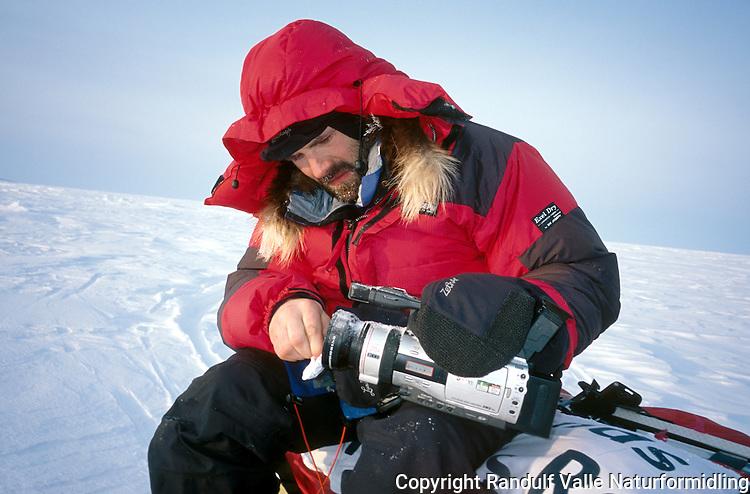 Mann med dunjakke pusser rim av videokamera. ---- Man cleaning lens on video camera.