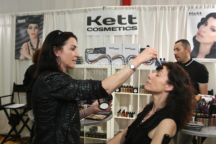 Sheila McKenna applies Kett Cosmetics makeup on to woman, during the Makeup Show NYC, in the Metropolitan Pavilion, May 15 2011.