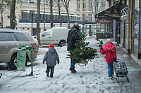 A father and his children taking a Christmas tree they have just bought home. Paris.
