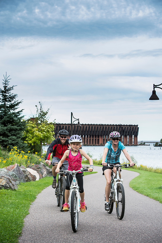 Family biking on the Iron Ore Heritage Trail along Lake Superior in Marquette, Michigan.