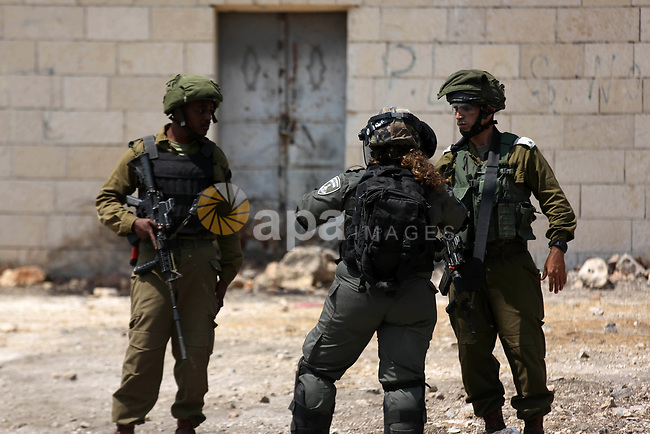 Israeli security forces take position during clashes with Palestinian protesters following a weekly demonstration against the expropriation of Palestinian land by Israel in the village of Kfar Qaddum, near the West Bank city of Nablus on July 19, 2019. Photo by Shadi Jarar'ah