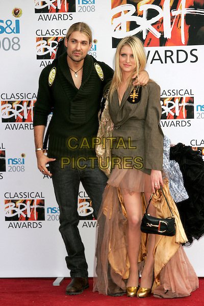 DAVID GARRATT & GUEST.Arrivals for the Classical Brit Awards 2008 held at the Royal Albert Hall, London, England, UK..May 8th, 2008.full length Garatt green jumper jeans jacket black frilly dress tutu skirt back behind bag gold shoes .CAP/AH.©Adam Houghton/Capital Pictures.