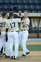 D.J. Poteet (4) of the Wake Forest Demon Deacons is greeted at home plate by his teammates after hitting a grand slam against the Liberty Flames at David F. Couch Ballpark on April 25, 2018 in  Winston-Salem, North Carolina.  The Demon Deacons defeated the Flames 8-7.  (Brian Westerholt/Four Seam Images)