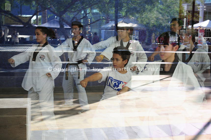 Mesa, Arizona. November 4, 2012 - A group of students of the U.S. Tae Kwon Do College in Arizona warm up before a presentation during the 18th Annual Asian Festival 2012 that took place at the Mesa Arts Center in Mesa, Arizona. The image was taking through the glass of the building. In Arizona, Asian-Americans celebrated a colorful festival where their rich culture was admired and their growing presence affirmed. Asian-Americans are now the United States fastest-growing racial group, the best-educated and highest-earning workers. Photo by Eduardo Barraza © 2012