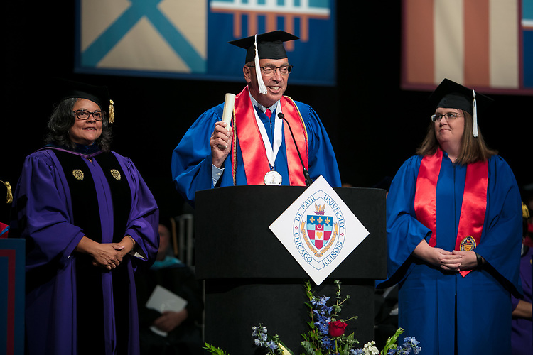 Marisa Alicea, dean of the School for New Learning, looks on as Jerry T. Lange, student speaker, inducts the graduating students into the Alumni Association with Nicole Guiffra-McQuaid, Class of 2011, Saturday, June 10, 2017, during the DePaul University School for New Learning commencement ceremony at the Rosemont Theatre in Rosemont, IL. (DePaul University/Jeff Carrion)