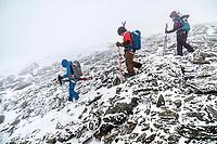 Skiers carrying their skis through rocks during a storm on the Öztal ski tour, Austria