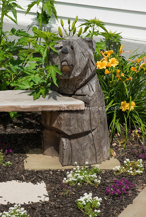 Bench with bear carving ornament with sweet alyssum Lobularia flowers, daylilies Hemerocallis Stella d'Oro, patio, mulch in the garden edging with pavers