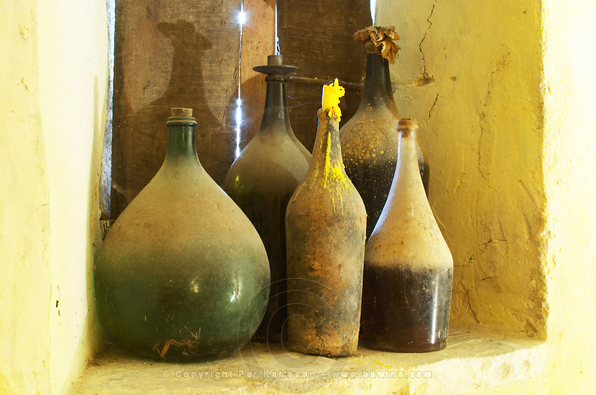 Chateau de Lascaux, Vacquieres village. Pic St Loup. Languedoc. Window. Old dusty bottles in the window. France. Europe. Bottle. One with a burnt down candle.