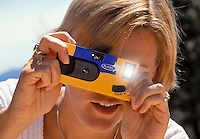 Young woman taking a flash photograph with a disposable camera..