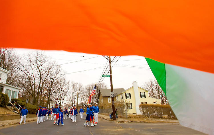 WATERBURY, CT--10 MARCH 2007--031007JS22- Members of the Prospect Drum Corps take a turn onto Keefe Street in Waterbury as they are framed by the Irish Tri-Color flag during the annual St. Patrick's Day parade in Waterbury on Saturday. The parade is organized by the Ancient Order of Hibernians. <br /> Jim Shannon / Republican-American