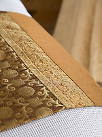 A detail of the gold-embroidered throw on the double bed of the master bedroom