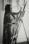 Beautiful young woman sumi-e artist with an easel painting naked in her home studio Black and white portrait