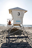 USA, California, San Diego, a woman watches the waves come from on top of lifeguard Tower 3 along Ocean Beach