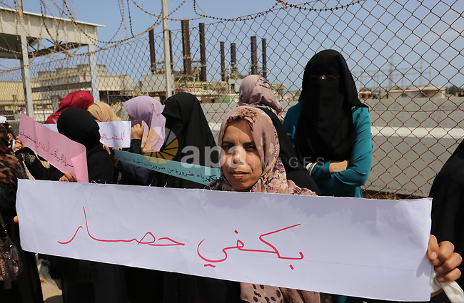 Palestinian women hold banners during a protest calling for an end to the power crisis, outside the power plant in the central Gaza Strip April 23, 2017. Photo by Ashraf Amra