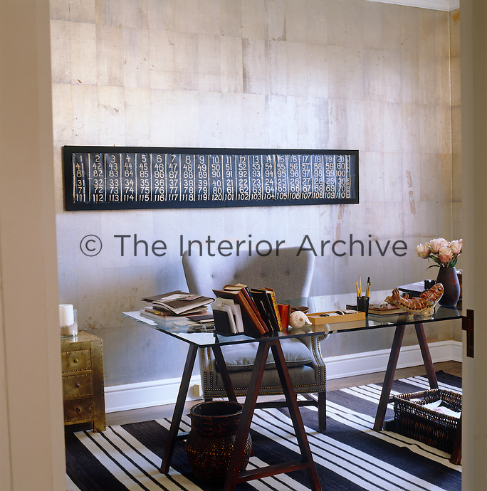 The walls of the study have been lined in stunning silver leaf and an armchair covered in tones of grey linen to match has been placed in front of a large trestle table with a clear glass top