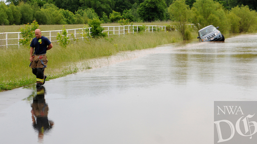 NWA Democrat-Gazette/J.T. WAMPLER --Fayetteville fire captain Jerry Kelly walks along a flooded Dead Horse Mountain Road in Fayetteville after emergency personnel helped a driver and passenger out of a vehicle when it left the roadway and became stuck in a flooded ditch Sunday May 17, 2015. No one was injured in the incident.