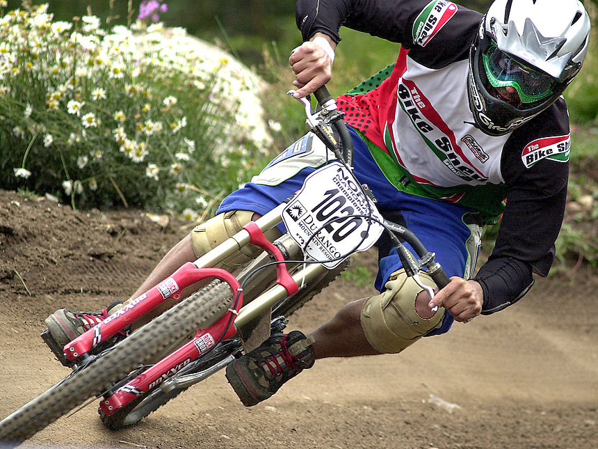 A downhill mountain bike racer (amateur) races in the 2003 NORBA national championship downhill race at Durango Mountain Resort in Durango, Colorado.