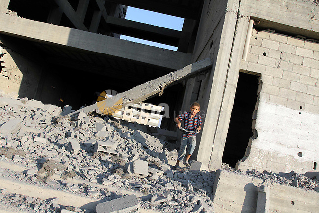 A Palestinian boy stands past a damaged government building after an Israeli air strike in Gaza August 19, 2011. Israeli aircraft struck Hamas security installations in Gaza on Friday, killing at least one Palestinian, in further retaliation for attacks along the Egyptian border in which eight Israelis died. Photo by Mohammed Asad